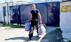 """Një i burgosur, duke lënë qelitë e burgut 325 në lagjen """"Ali Demi"""", pas hyrjes në fuqi të ligjit për amnistinë, ku 900 të dënuar dhe të paraburgosur u liruan para kohe më 10 prill 2014. Fytyra i është mbuluar për t'i ruajtur privatësinë. Foto: LSA"""